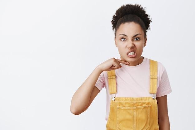 Je bent dodelijk. portret van een boze, pissige jonge vrouwelijke student met een donkere huid in gele overall, duim boven het gezicht houdend, iemand bedreigend om een persoon te doden en de nek door te snijden, woedend en eng te zijn