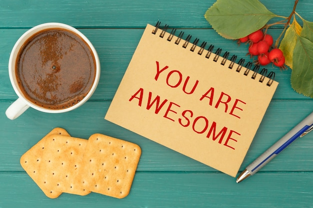 Je bent geweldig - een inscriptie op een notitieboekje, warme koffie en koekjes op een houten tafel
