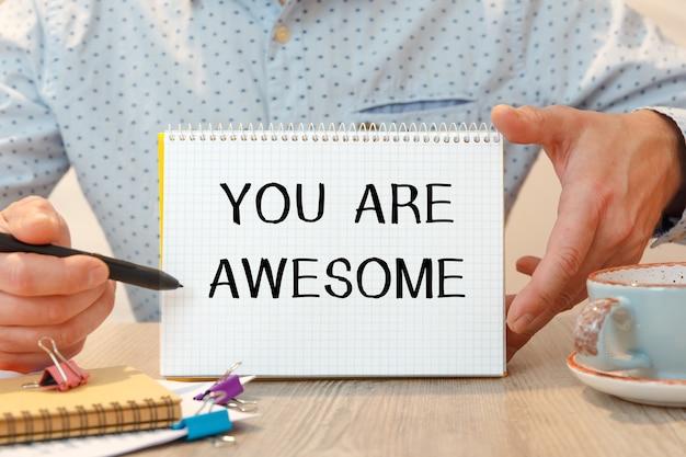 Je bent geweldig staat geschreven op een notitieblok op een bureau met kantooraccessoires.