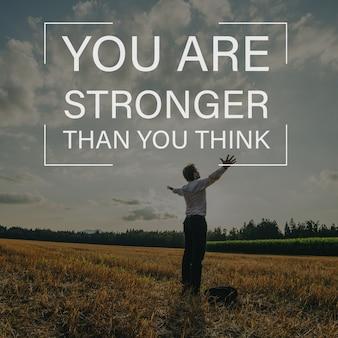 Je bent sterker dan je denkt, teken boven een zakenman die in de natuur staat met zijn armen wijd gespreid onder de avondhemel.
