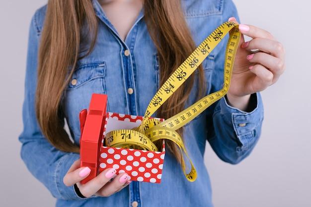 Je bent te dik! naar de sportschool! bijgesneden close-up foto van verbaasde vette dame met opening uitpakken uitpakken pakket met gele meter geïsoleerde grijze achtergrond