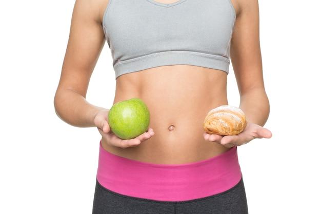 Je bent wat je eet. bijgesneden shot van een fitte vrouw met een strakker lichaam met een appel en een croissant in de buurt van haar platte buik