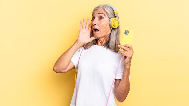 Je blij, opgewonden en verrast voelen, opzij kijken met beide handen op het gezicht met een koptelefoon