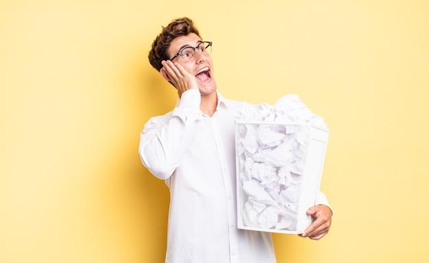 Je blij, opgewonden en verrast voelen, opzij kijkend met beide handen op het gezicht. prullenbak papier concept