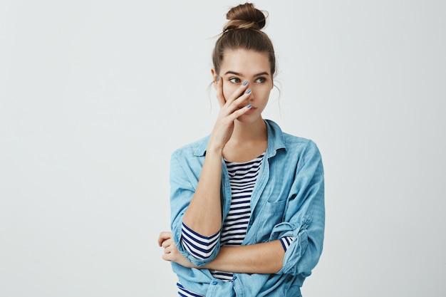 Je bracht me in verlegenheid voor vrienden. portret van geïrriteerde jonge europese vrouw in broodje kapsel en denim shirt, hand in hand op gezicht en opzij kijken, teleurgesteld of ontevreden