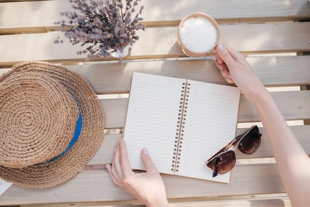 Je dag plannen. jong meisje met een notebook neemt een kopje koffie. bovenaanzicht Premium Foto