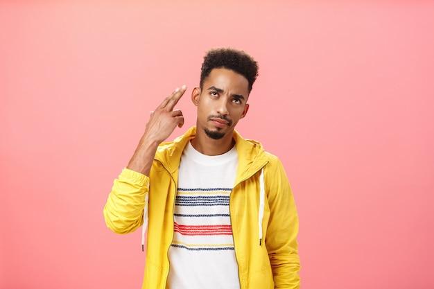 Je doodt mijn vibe. sombere geïrriteerde en geërgerde knappe, stijlvolle afro-amerikaanse man in een geel trendy jasje met een vingerpistoolgebaar over de tempel alsof hij zichzelf neerschoot met een verontruste blik
