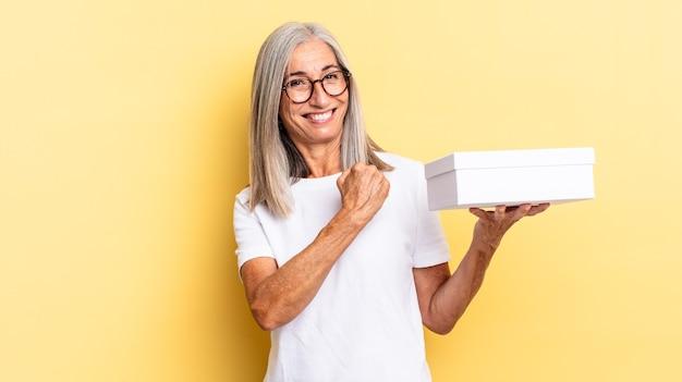 Je gelukkig, positief en succesvol voelen, gemotiveerd zijn wanneer je voor een uitdaging staat of goede resultaten viert en een witte doos vasthoudt