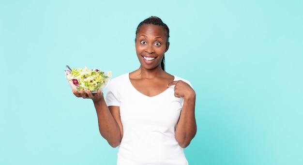 Je gelukkig voelen en naar jezelf wijzen met een opgewonden gevoel en een salade vasthouden