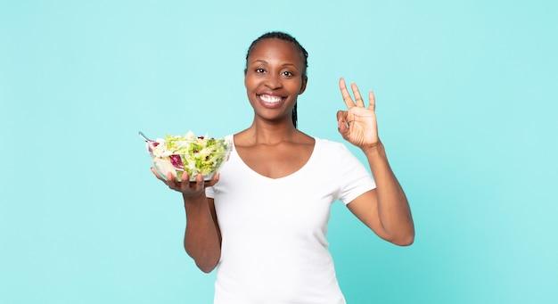 Je gelukkig voelen, goedkeuring tonen met een goed gebaar en een salade vasthouden