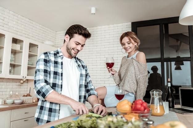 Je goed voelen. donkerharige knappe man in een geruit overhemd glimlachend helder tijdens het snijden van groenten voor het ontbijt