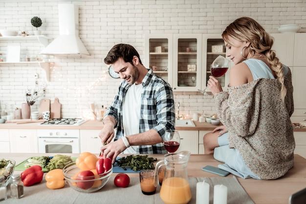 Je goed voelen. donkerharige knappe man in een geruit overhemd kijkt tevreden terwijl hij groenten snijdt voor het ontbijt