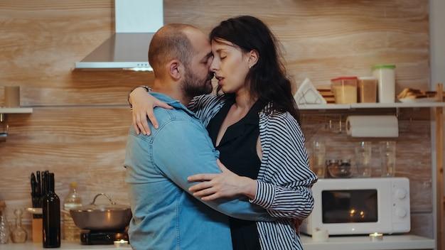 Je goed voelen tijdens een romantisch diner, dansend en lachend. gelukkig getrouwd verliefd stel dat samen thuis eet, geniet van de maaltijd, plezier heeft, hun jubileum viert.