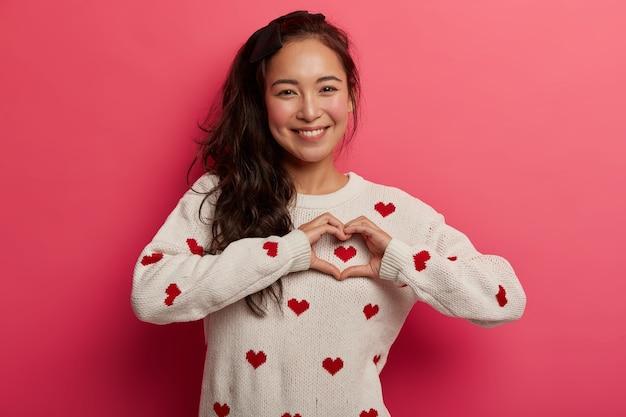 Je hebt de sleutel tot mijn hart gevonden. mooie glimlachende koreaanse vrouw maakt een teken van liefde, drukt tedere gevoelens uit, heeft een paardenstaart, een gezonde huid, draagt een trui, heeft een romantische bui. dames