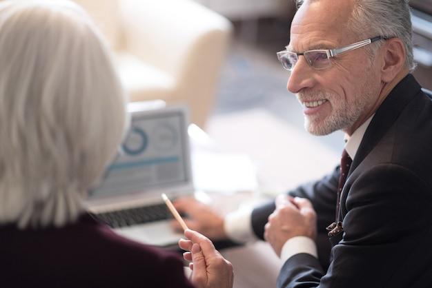 Je hebt een interessant idee. vrolijke opgetogen oude zakenman die lacht en op kantoor zit voor de laptop terwijl hij met zijn collega werkt en interesse toont