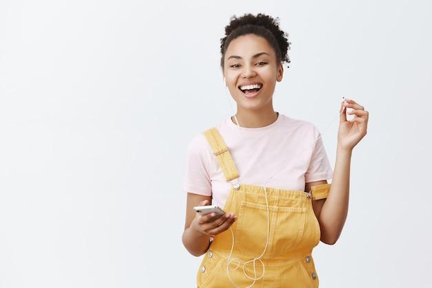 Je hebt iets gevraagd. portret van zorgeloos ontspannen en gelukkig afro-amerikaanse vrouw in trendy overall, oortelefoon opstijgen om vriend te horen, breed glimlachend, smartphone vasthouden, muziek luisteren