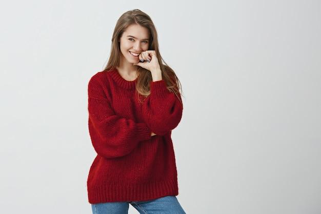 Je hebt mijn aandacht getrokken. studio shot van positieve aantrekkelijke vrouwelijke collega in trendy losse trui met vinger op lip terwijl lachend met interesse of verlangen, luisterend naar knappe jongen
