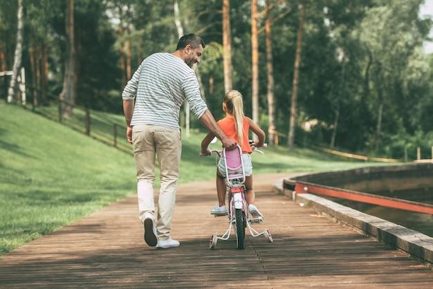 Je kunt het! achteraanzicht van de volledige lengte van een vrolijke vader die zijn dochter leert fietsen in het park