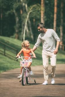 Je kunt het! volledige lengte van vrolijke vader die zijn dochter leert fietsen in het park