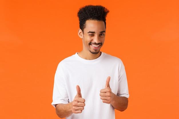 Je kunt het, zeg ja. vrolijke en zelfverzekerde jonge ondersteunende afro-amerikaanse man in een wit t-shirt, knipoog en glimlach, met een duim omhoog gebaar, wortel schieten, alles aanmoedigen goed, mooi werk