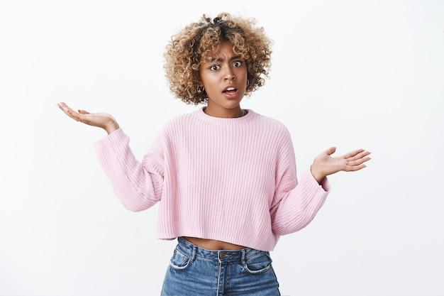 Je let op je mond. portret van beledigde, pissige afro-amerikaanse vrouw met blond kapsel die handen zijwaarts opheft in ontzetting, geschokt en beledigd poseren verward over witte muur, boos