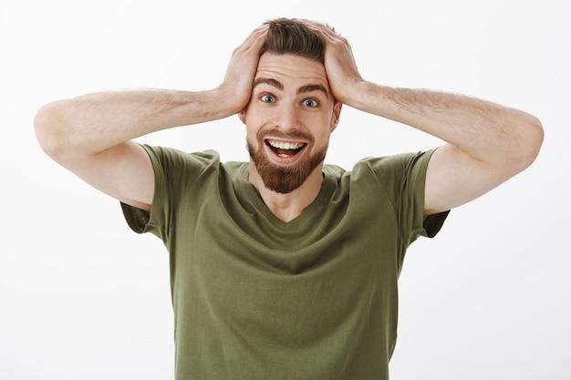 Je maakt geen grapje. blij verbaasd en verrast opgewonden knappe man met baard in olijfgroen t-shirt pak het hoofd met de handen en lachend van verbazing en opwinding, de eerste prijs winnen