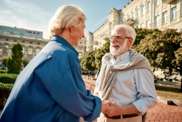 Je maakt me blij, mooi bejaarde echtpaar hand in hand en kijkend naar elkaar met een glimlach