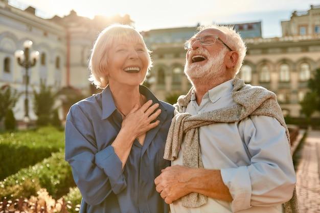 Je maakt me een gelukkig portret van een mooie en stijlvolle senior die lacht terwijl hij in het park staat