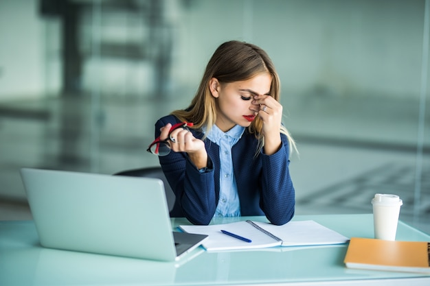 Je moe en gestrest voelen. gefrustreerde jonge vrouw die de ogen gesloten houdt en de neus masseert terwijl ze op haar werkplek op kantoor zit