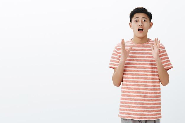 Je moet me geloven. overreacterende opgewonden en geschokte jonge aziatische kerel met donker kort kapsel, open mond naar adem happen en handen opsteken terwijl hij geweldig nieuws uitlegt aan de rechterkant van de kopie ruimte