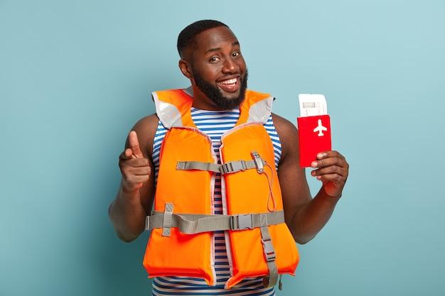 Je moet mee op reis! blij glimlachende ongeschoren donkere man houdt instapkaart en paspoort vast, draagt een reddingsvest