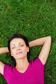 Je ontspannen en vredig voelen. bovenaanzicht van een mooie jonge vrouw die slaapt terwijl ze de handen achter het hoofd vasthoudt en op het groene gras ligt