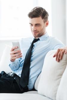 Je op je gemak voelen tijdens het zakendoen. glimlachende jonge zakenman die mobiele telefoon houdt