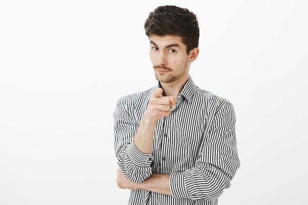 Je uitkiezen om te werken in mijn team van leiders. geïntrigeerde knappe slimme man in gestreept overhemd, wijzend met wijsvinger, kijkend van onder voorhoofd met nieuwsgierig gezicht, met suggestie
