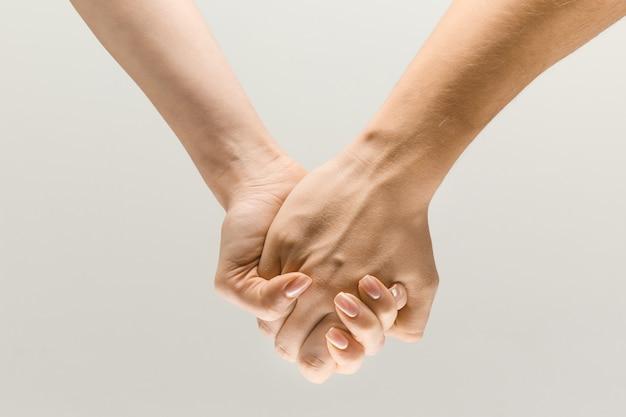 Je verder leiden. lossup shot van mannelijke en vrouwelijke hand in hand geïsoleerd op grijze studio achtergrond. concept van menselijke relaties, vriendschap, partnerschap, familie. kopieerruimte.