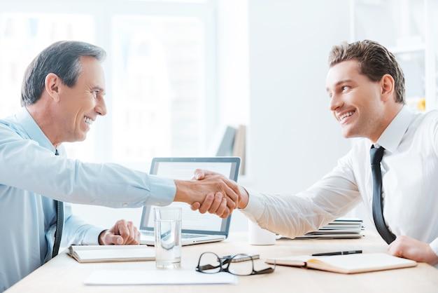 Je verdient je succes. zijaanzicht van twee zakenmensen die handen schudden