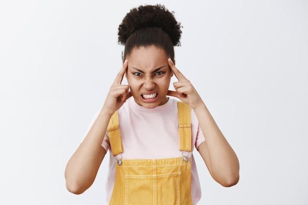 Je vermoorden met kracht van geest. portret van boze donkere vrouwelijke student in gele overall, wijsvingers op tempel, starend met haat en agressie over grijze muur