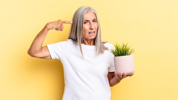Je verward en verbaasd voelen, laten zien dat je gek, gek of gek bent terwijl je een decoratieve plant vasthoudt