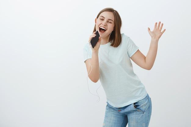Je voelt je als een populaire zanger op het podium. geamuseerd en energiek vrouw in t-shirt kantelen lichaam dansen en hoofd zwaaien luisteren muziek in oortelefoons met gesloten ogen zingen op smartphone zoals in microfoon