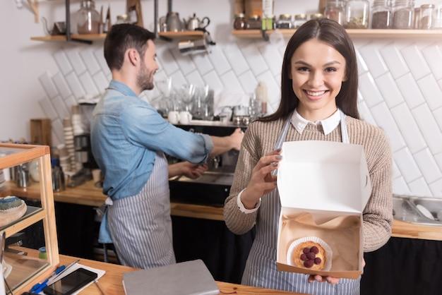 Je wordt er blij van. mooie gelukkige vrouw die en doos met cake glimlacht houdt terwijl haar partner koffie voorbereidt.