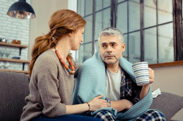 Je zal beter worden. aardige zorgzame vrouw die naast haar zieke man zit terwijl ze hem steunt