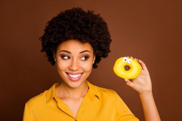 Je ziet er zo lekker koekje uit! close-up foto van funky donkere huid dame houdt kleurrijke donut karamel ogen menselijke gezichten schilderen wat eet gele shirt geïsoleerde bruine kleur