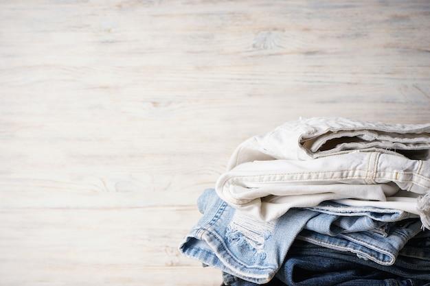 Jeans broek stapel op lichte houten achtergrond, ruimte voor tekst.