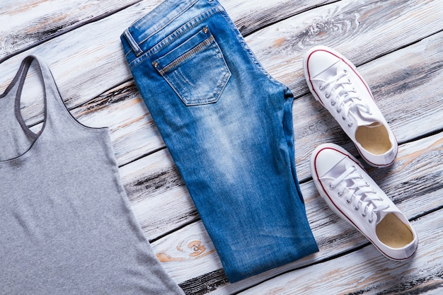 Jeans en grijze tanktop. canvas schoenen en opgevouwen broek. dameskleding op witte tafel. leuke vrijetijdskleding met schoeisel.