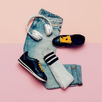 Jeans en sneakers. kniekousen. urban active-outfit. koptelefoon. bovenaanzicht. minimaal ontwerp
