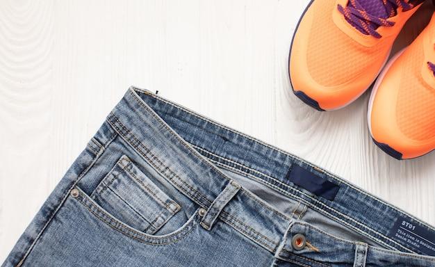 Jeans en sneakers plat uitzicht op houten achtergrond