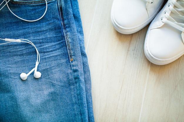 Jeans en witte sneakers op de plank