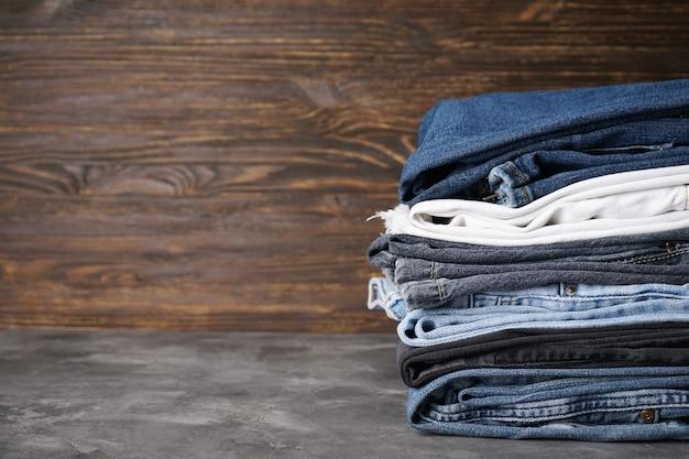Jeans gestapeld in een stapel, op een houten achtergrond, ruimte voor tekst.