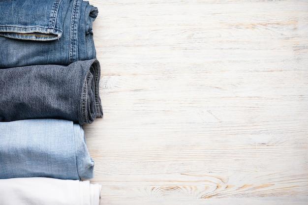 Jeans gestapeld op een houten tafel, bovenaanzicht. ruimte voor tekst.