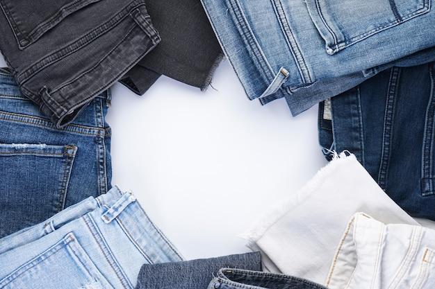 Jeans gestapeld op witte achtergrond, bovenaanzicht. ruimte voor tekst.